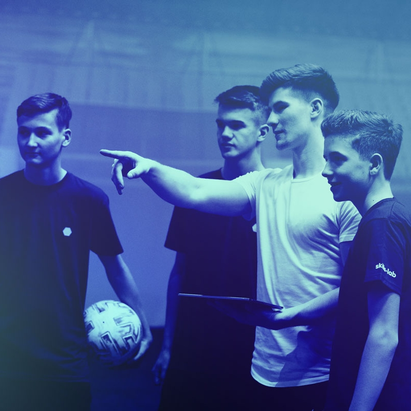 A skills.lab coach giving instructions to three youth players during an open training