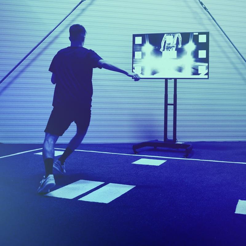 Bild zeigt einen jugendlichen Spieler beim Training im Speedcourt. Zwei weitere Jugendliche sehen zu.