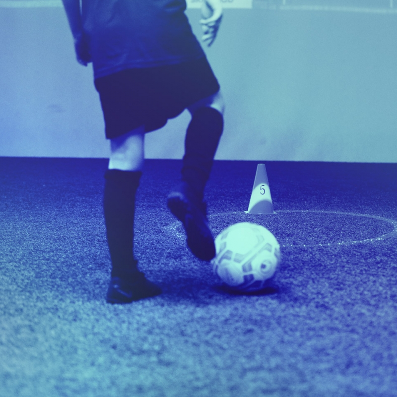 Detail shot of a kid in the skills.lab Arena with a ball on his right foot