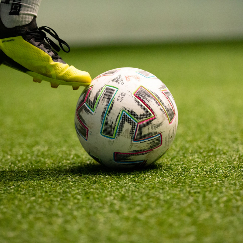 Detailaufnahme eines Spielerbeins und eines Balls