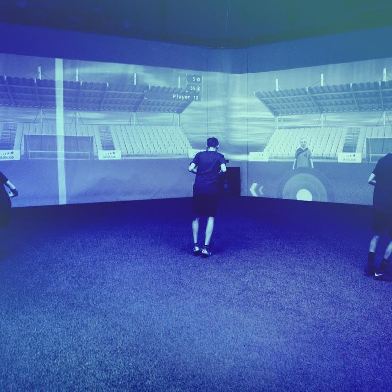 Aufnahme von drei jugendlichen Spielern bei einer Passübung in der skills.lab Arena