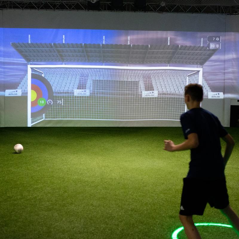 Aufnahme von hinten zeigt einen jugendlichen Fußballer bei einer Torschussübung in der skills.lab Arena