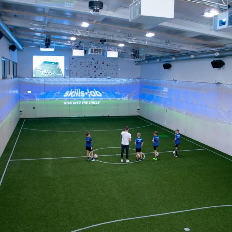 Blog - Innenaufnahme der KIB Sport One Arena während der Eröffnungsfeier mit einem Trainer und mehreren Nachwuchsspielern