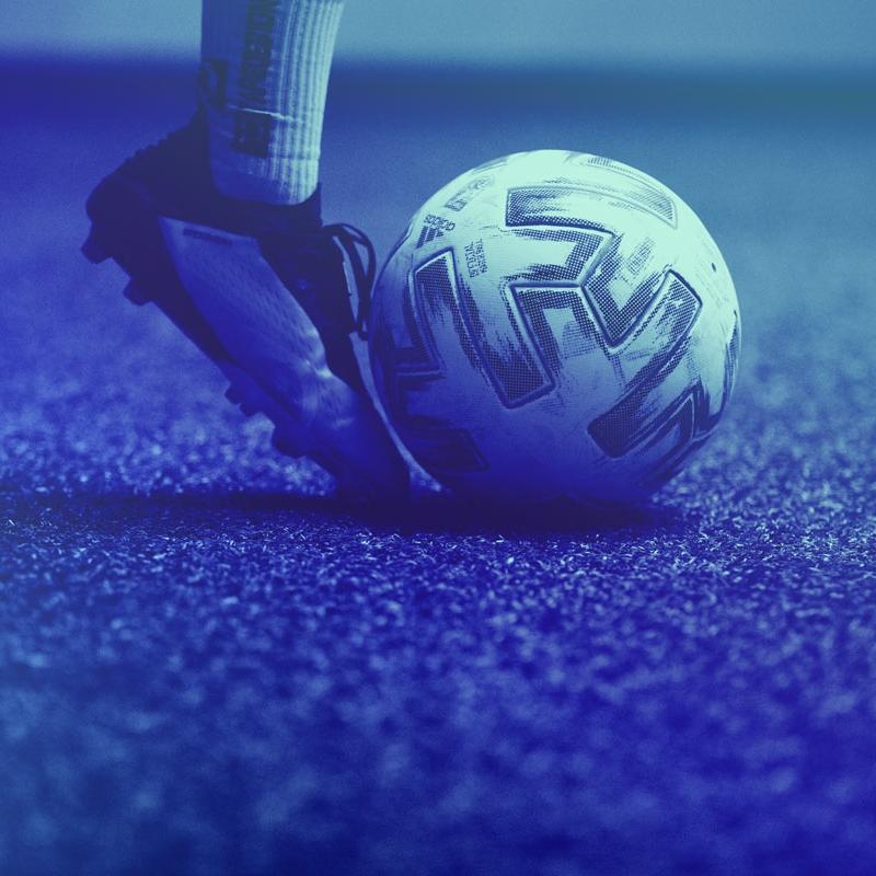 Detailaufnahme eines Fußballspieler, der einen Ball an seinem rechten Fuß führt