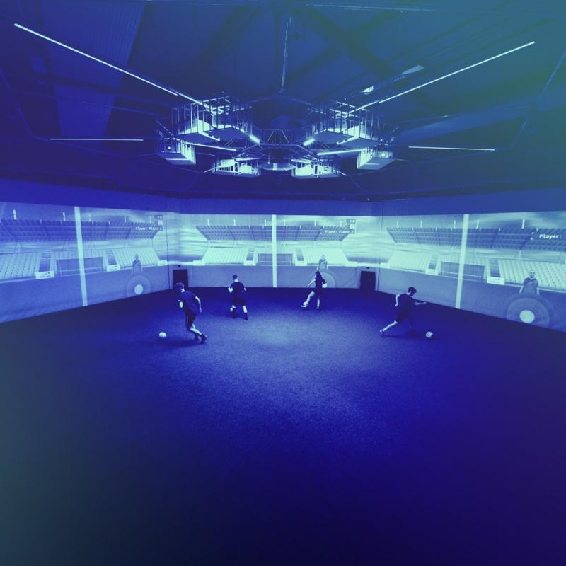 Panoramaaufnahme von vier erwachsenen Spielern bei einer Parallelpassübung in der skills.lab Arena
