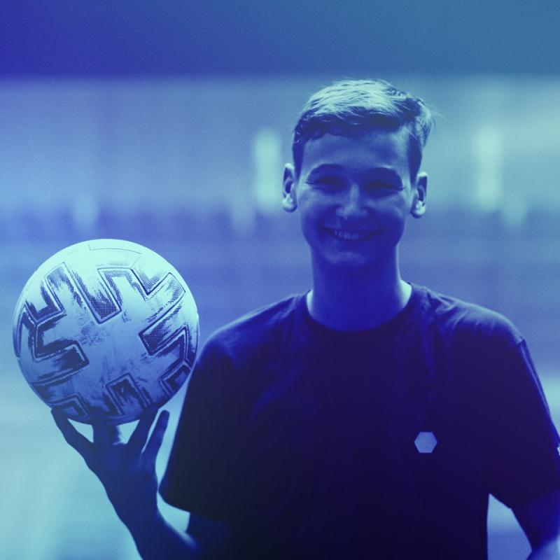 Porträtaufnahme eines jugendlichen Spielers mit Ball in seiner rechten Hand
