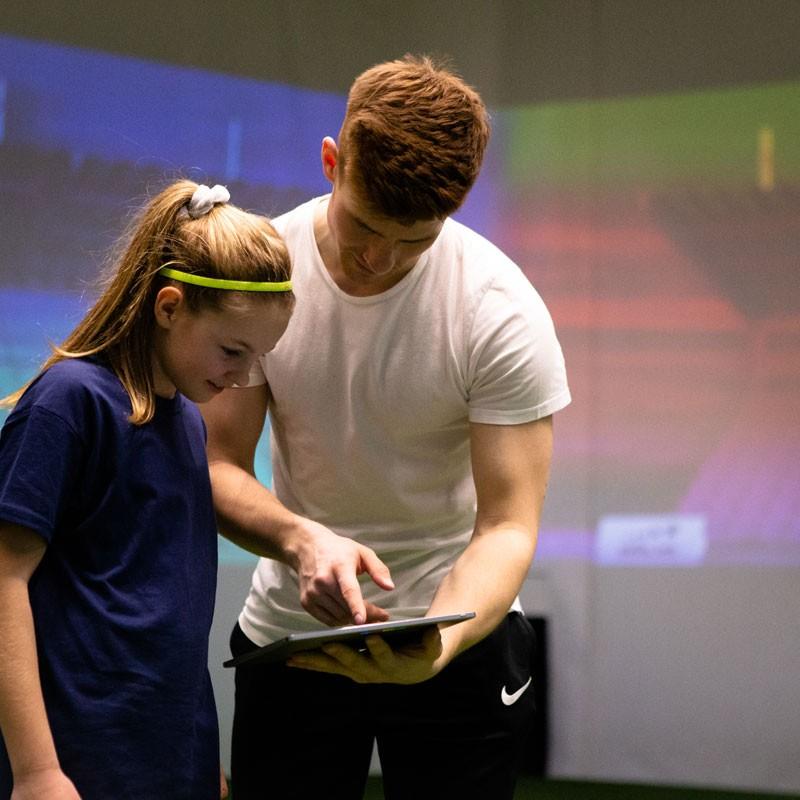 Skills Check Kinder - Ein skills.lab Coach gibt Anweisungen an eine Nachwuchsspielerin